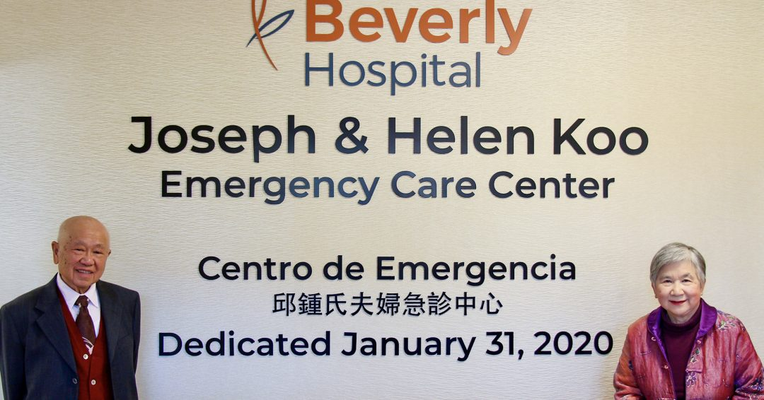 Joseph and Helen Koo stand next to another dedication sign which is located right inside the Emergency Care Center Entrance. The sign reads Joseph & Helen Koo Emergency Care Center in English, Spanish, and Chinese.